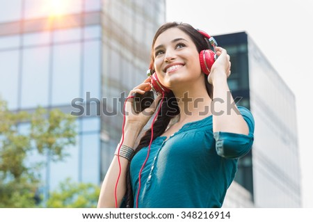 Closeup shot of young woman listening to music with mobile phone in the city center. Happy smiling girl listening to music with professional red headset. Beautiful brunette  young woman feeling free. - stock photo
