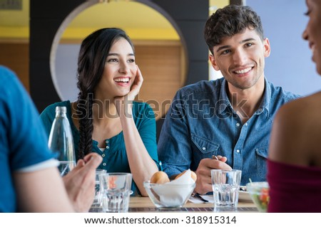 Closeup shot of young women and men having meal. Happy smiling friends eating together at restaurant. Girls and guys are having fun during lunch. - stock photo
