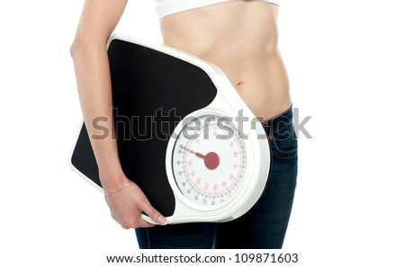 Closeup shot, woman carrying weighing machine. Cropped image