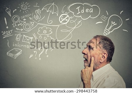 Closeup side profile portrait thoughtful senior man has many ideas looking up isolated on gray wall background  - stock photo