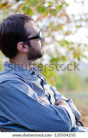 Closeup side view of a bearded man sitting enjoying the sunshine looking away from the camera into a garden or park