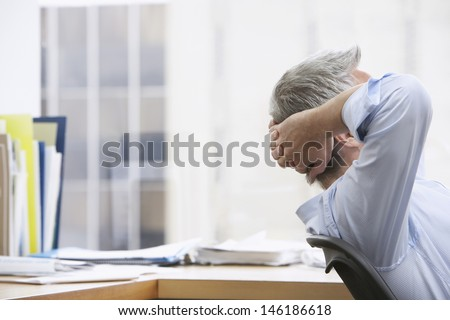 Closeup side view of a businessman with hands behind head in office - stock photo