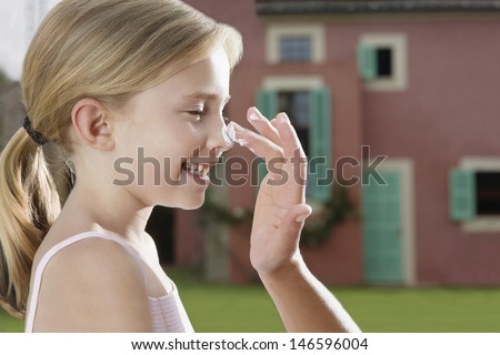 Closeup side view of a hand applying sunscreen to smiling daughter's nose outdoors - stock photo