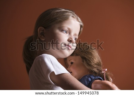 Closeup side view of a little girl embracing her doll - stock photo