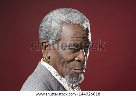 Closeup side view of a senior African American man with earrings against red background - stock photo