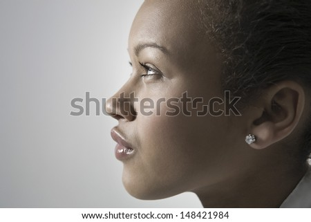 Closeup side view of a thoughtful African American young woman against gray background - stock photo
