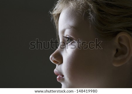 Closeup side view of a young girl against black background - stock photo