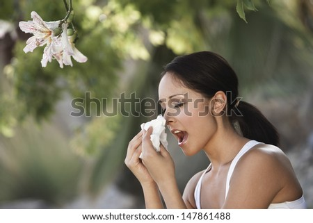 Closeup side view of a young woman sneezing by flowers - stock photo