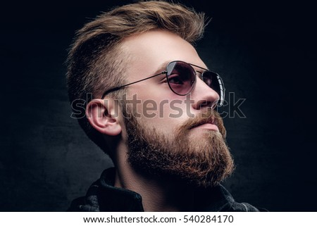 Closeup side view of bearded male in sunglasses on grey vignette background.