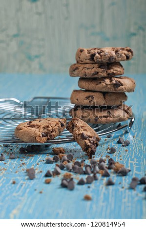 Closeup side view of biscuits with chocolate drops on round iron stand on cracked blue background - stock photo