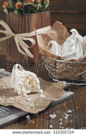 Closeup side view of broken meringue with crumbs on brown paper and lot of meringues in iron bowl on dark wooden background - stock photo