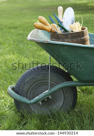 Closeup side view of cropped wheelbarrow with gardening tools on grass - stock photo