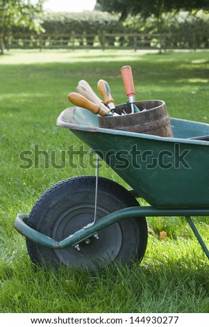 Closeup side view of cropped wheelbarrow with gardening tools on grass