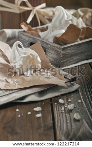 Closeup side view of half of meringue and crumbs on paper and wooden box with meringues on dark wooden background - stock photo