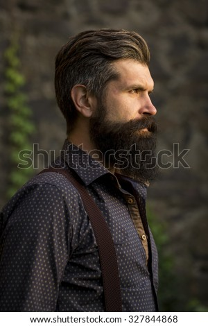 Closeup side view of one handsome senior man with black hair and long lush beard in blue shirt and purple trausers standing outdoor on stone wall grey background, vertical picture - stock photo