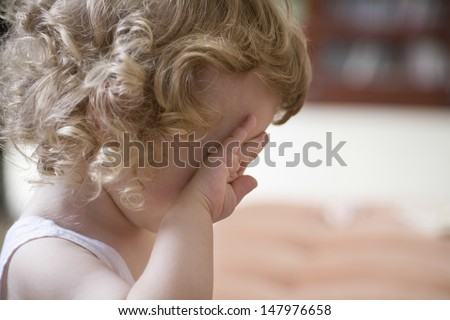 Closeup side view of unhappy baby boy rubbing eye at home - stock photo