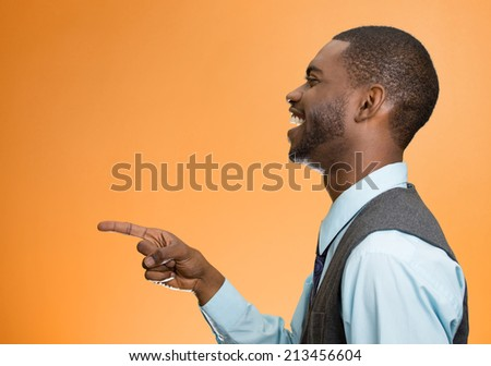 Closeup side view portrait happy young man, laughing, pointing with finger at someone, something, isolated orange background. Positive human face expressions, emotions, feelings, attitude, approach - stock photo