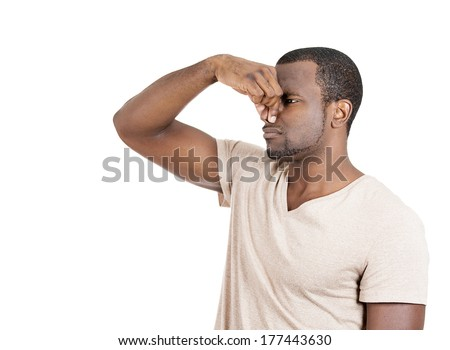 Closeup side view portrait of young man, disgust on face, pinches his nose, something stinks, very bad smell, situation, isolated on white background. Negative human emotion facial expression feeling - stock photo