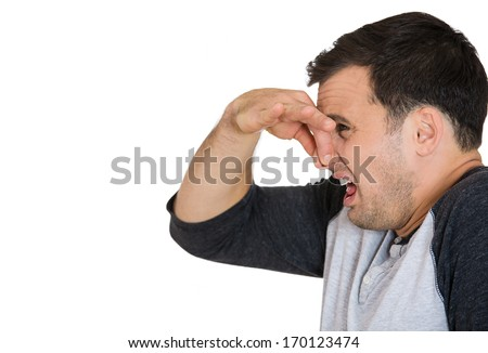 Closeup side view portrait of young man, disgust on his face, pinches his nose, something stinks, very bad smell, situation, isolated on white background. Negative emotion facial expression feeling - stock photo