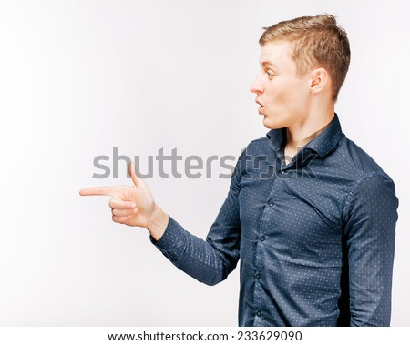 Closeup side view portrait of young man, laughing, pointing with finger at someone or something. Positive human face expressions, emotions, feelings, attitude, approach - stock photo
