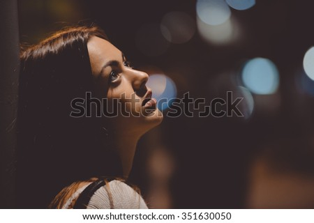 Closeup side view portrait of young sad thoughtful woman leaning against street lamp at night on bokeh copy space background - stock photo