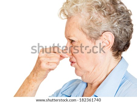 Closeup side view portrait old lady, senior executive, grandmother, disgust on her face, pinching nose something stinks, displeased with situation, isolated white background. Interpersonal conflict - stock photo