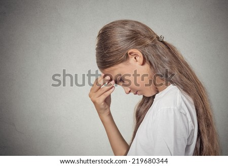 Closeup side view portrait sad tired disappointed teenager girl face on hand looking down isolated grey wall background. Negative human emotion facial expression feeling life perception body language - stock photo