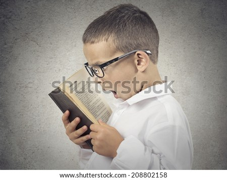 Closeup side view profile portrait, Headshot funny looking, Shocked Boy Reading story, Book, history isolated grey background. Human face expressions, emotions, reaction, body language, perception.  - stock photo