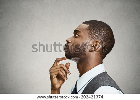 Closeup side view profile portrait, headshot young man daydreaming deeply about something with chin on hand looking upwards, isolated black background space to left. Emotion facial expressions feeling - stock photo
