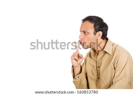 Closeup side view profile portrait of handsome man  in brown shirt placing fingers on lips as if to say shhh, isolated on white background with copy space - stock photo