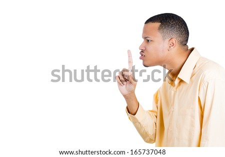 Closeup side view profile portrait of young serious man placing finger on lips to say shhhhh, be quiet silence isolated on white background, space to left. Facial expression emotions signs and symbols - stock photo