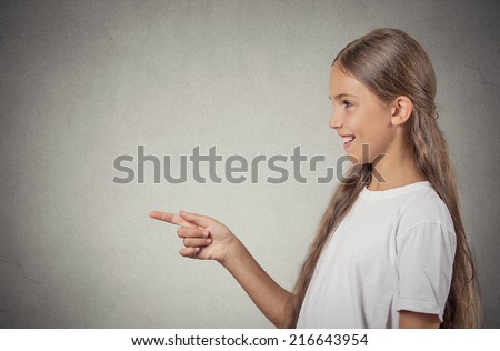 Closeup side view profile portrait, teenager girl pointing, surprised by something or someone, isolated grey wall  background with copy space. Positive human emotion facial expression feeling reaction - stock photo