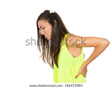 Closeup side view profile portrait young woman, undergraduate student, looking miserable, holding lower back with hands, doubling over in pain, isolated white background. Face expression - stock photo
