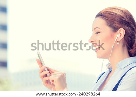 Closeup side view woman with earphones holding using smart mobile phone isolated outside corporate building background. People new generation technology concept. Customer service provider relationship - stock photo