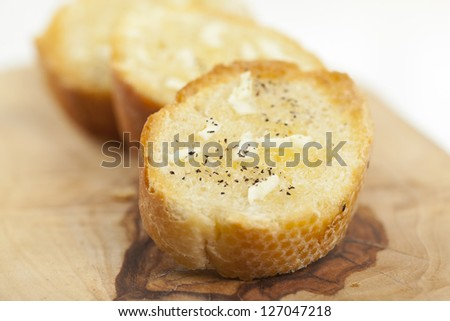 Closeup slices with garlic spread over a wooden chopping board - stock photo
