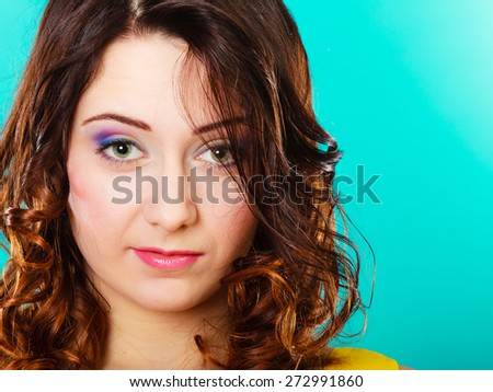 Closeup smiling woman face, girl with long brown curly hair colorful makeup portrait on green