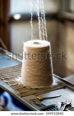 Closeup Spool of brown Thread on Industrial Sewing Machine - stock photo