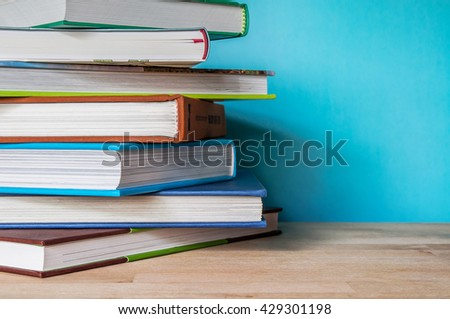 Closeup Stack of colorful books on wooden table with blue background. Time to learn and read concept.  - stock photo