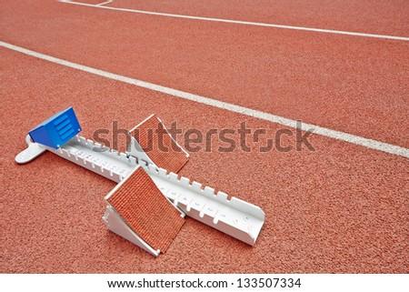 Closeup starting blocks on red race track - stock photo