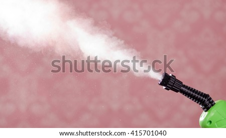 Closeup steam exiting nozzle of vapor cleaning machine, pink background - stock photo