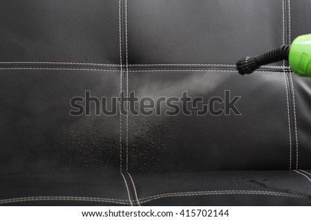 Closeup steam exiting nozzle of vapor cleaning machine, rinsing black leather couch - stock photo