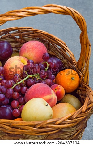 Closeup still life of ripe purple grapes, red peach, orange tangerine and violet plums in a basket, summer, harvest