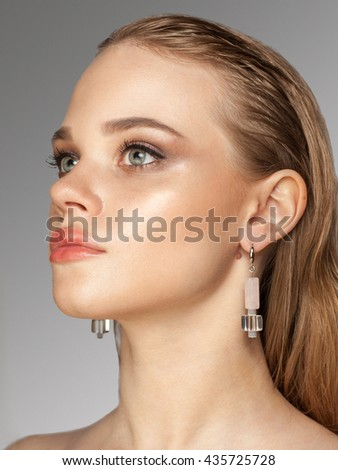 closeup studio beauty portrait of young blonde caucasian female model with wet hair, blue eyes, professional makeup isolated on gray background - stock photo