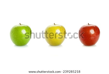 Closeup studio photo of green, yellow and red apples isolated on white background with soft shadow and reflection. Traffic lights color scheme concept
