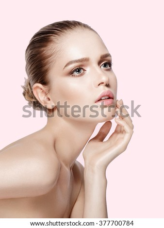 Closeup studio portrait of beautiful model with professional makeup on pink background. Perfect skin. Blue eyes. Brunette hair. Soft colors. Not isolated - stock photo