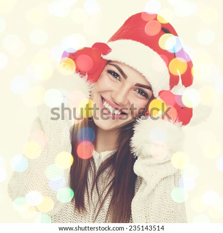 Closeup studio portrait of happy young Christmas woman with Santa Claus hat. Colorful bokeh blur light effect. Square format image. - stock photo
