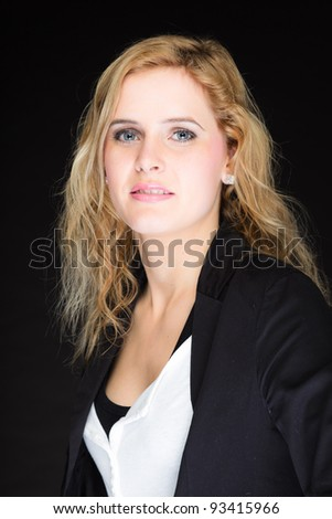 Closeup studio portrait of pretty young woman with pink lipstick and long blond hair. Wearing a black suit. Isolated on black background. - stock photo