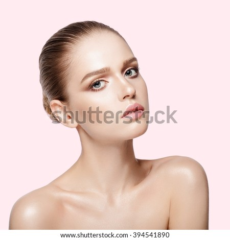 Closeup studio portrait of young attractive model with professional makeup on pink background. Perfect skin. Blue eyes. Brunette hairdo. Not isolated - stock photo