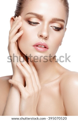 Closeup studio portrait of young beautiful model with professional makeup on white background. Perfect fresh clean skin. Deep blue eyes. Brunette hair. Hands touching face. Isolated - stock photo