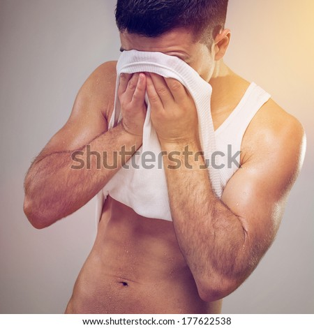 Closeup studio shot of fit tired young Caucasian man wiping sweat off his face with his shirt. Fitness, workout, sport and healthy lifestyle. Retro vintage filter applied.  - stock photo